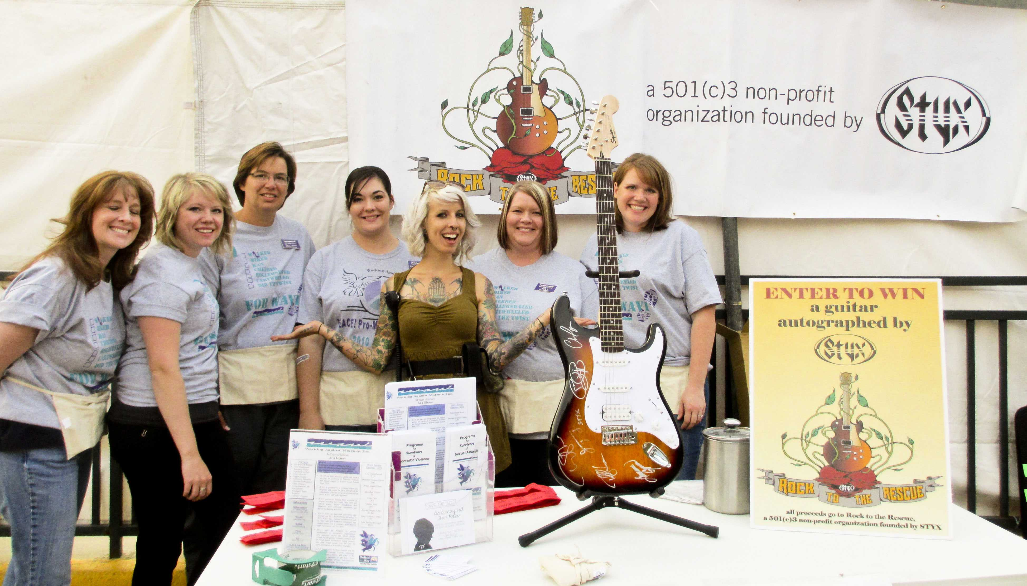 Hannah Shaw executive director of Rock to the Rescue (center) partner with Rapid City WAVI volunteers from Left: Kelley Crane, Mallory Heutzenroeder, Mary Corbine (Executive Director of WAVI), Rebekkah Kruse, Ruth Torala and Morgan VonHaden to manage raffle ticket sales.