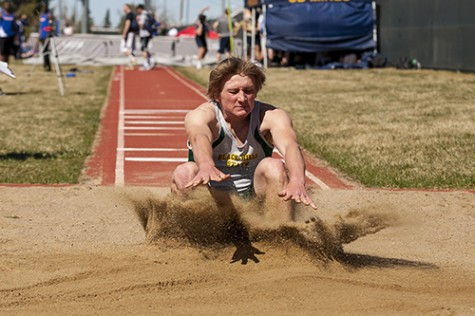 Ryan Mehalick lands in the sand pit during the men's long jump event.