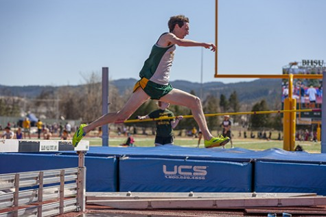 Mitch Kraft clears the hurdle before landing in the water pool during the men's steeplechase.