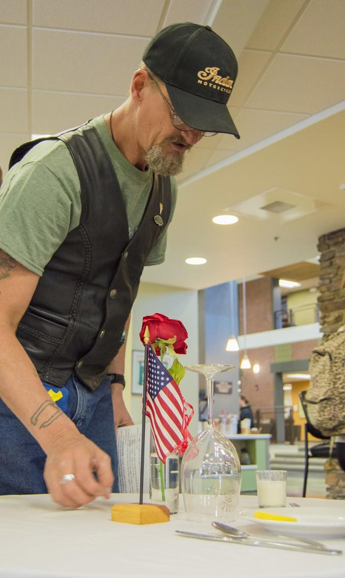 Veterans' Club member Steve Weir puts the finishing touches on the Missing Man table in the Student Union Sept. 17 in observance of National POW/MIA Recognition Day. The table and its elements are put in place to honor and remember fallen, missing, or imprisoned military members
