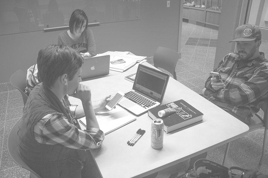 Students sit and text on their phones while studying in Jonas cubicles