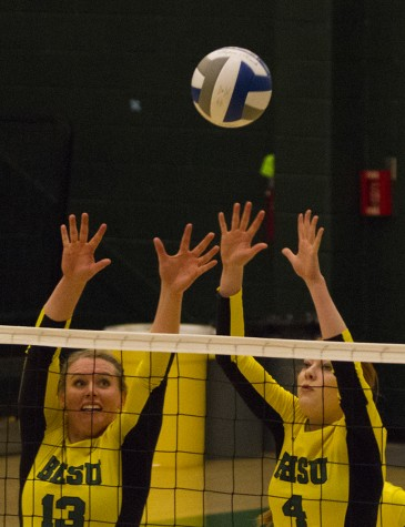 Shelby Mayer (13) and Kenzie Kazmer (4) go up to block a shot during their Oct. 10 game with Regis.