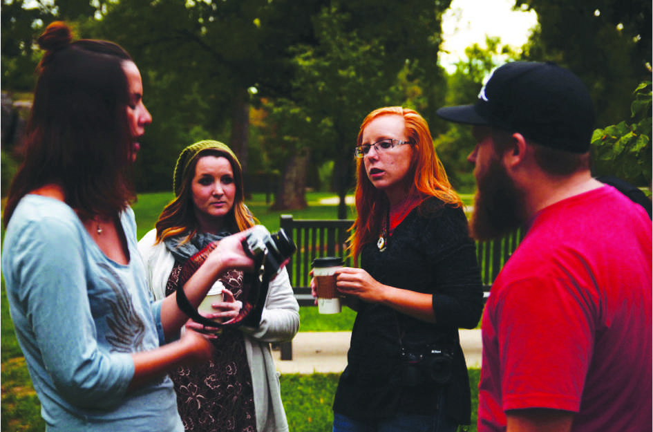 Taylor Stone (third from left) assists fellow club member with her film camera.
